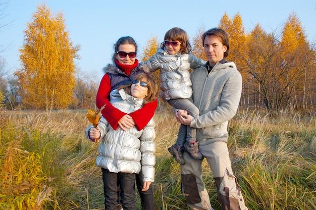 Gelukkige glimlachende familie die in de herfstpark loopt. ouders met kinderen buitenshuis