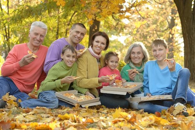 Gelukkige glimlachende familie die pizza eet in het herfstpark