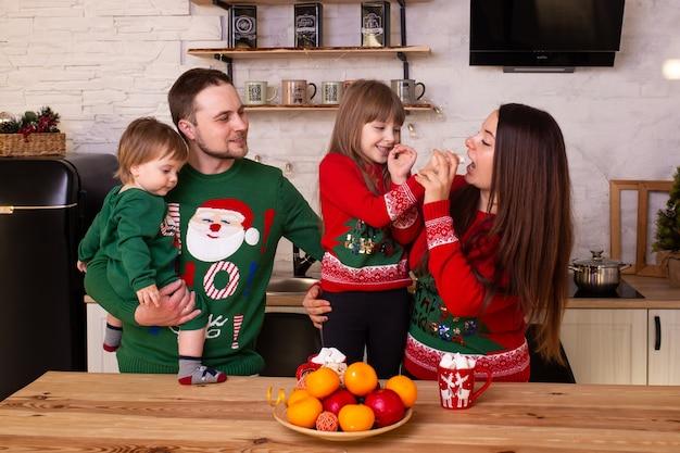 Gelukkige glimlachende familie in de keuken in nieuwjaar thuis