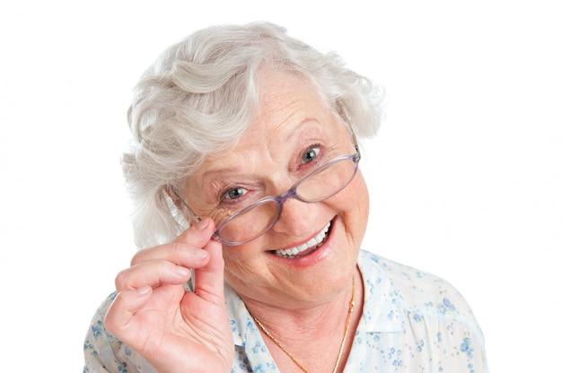 Gelukkige glimlachende gepensioneerde dame die haar nieuwe bril draagt die op wit wordt geïsoleerd