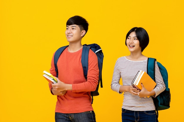 Gelukkige glimlachende jonge aziatische studenten die boeken dragen aan school