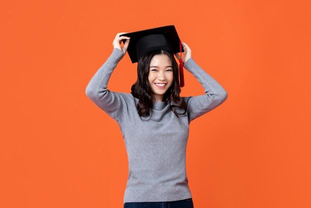 Gelukkige glimlachende jonge aziatische vrouw die graduatie glb draagt