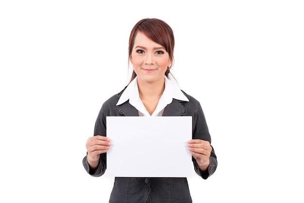 Gelukkige glimlachende jonge bedrijfsvrouw die leeg uithangbord, over witte achtergrond houdt