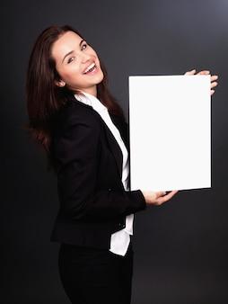 Gelukkige glimlachende jonge bedrijfsvrouw die leeg uithangbord toont