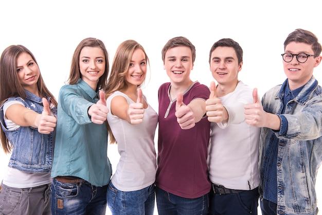 Gelukkige glimlachende jonge groep vrienden met omhoog duimen.