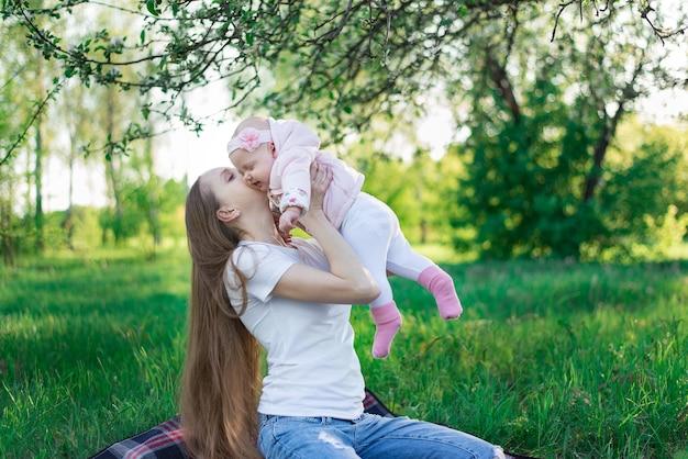 Gelukkige glimlachende jonge moeder die weinig babydochter over aardoppervlak houdt