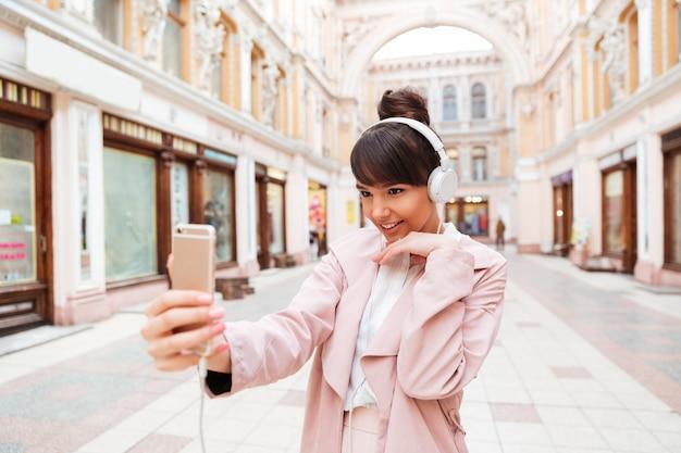 Gelukkige glimlachende jonge vrouw die in hoofdtelefoons selfie foto maken