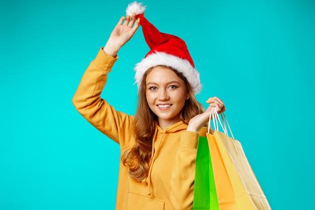 Gelukkige glimlachende jonge vrouw die in kerstmanhoed het winkelen zakken tegen blauw houden
