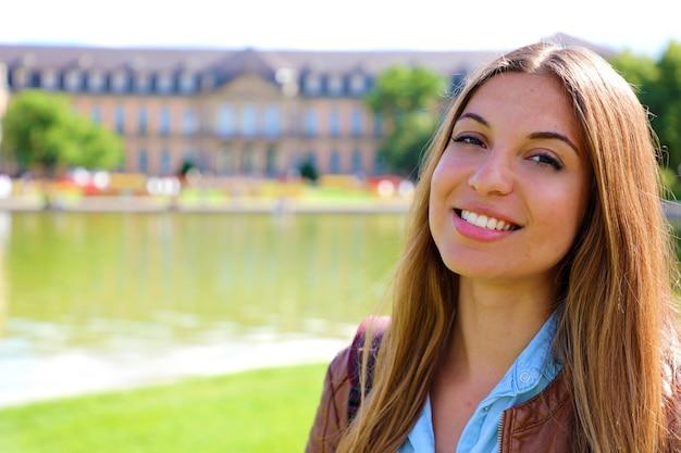 Gelukkige glimlachende jonge vrouw voor neues schloss (nieuw paleis) van stuttgart, duitsland