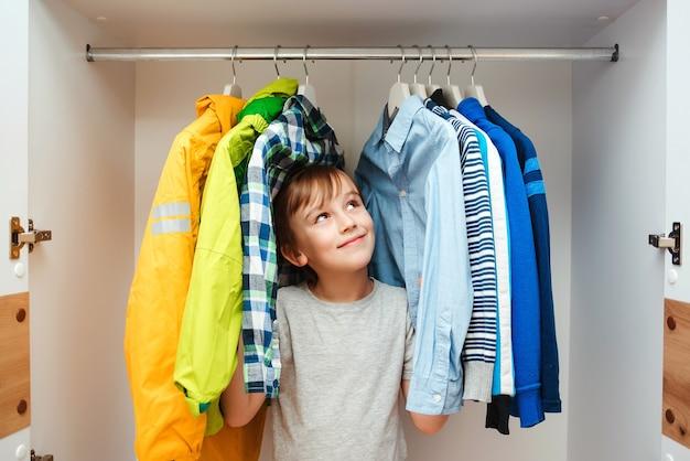 Gelukkige glimlachende jongen die naar kleding in een kast zoekt. preteen jongen kiest kleren in de garderobekast thuis. kind verstopt onder kleren in de kledingkast.