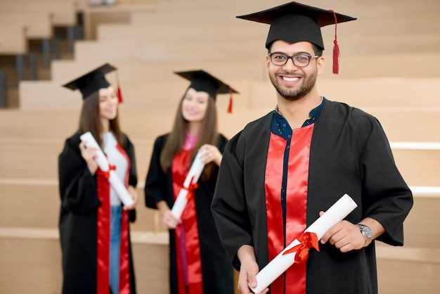 Gelukkige glimlachende jongen die universitair diploma houdt.