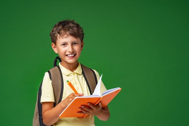 Gelukkige glimlachende jongen die voor school voorbereidingen treft