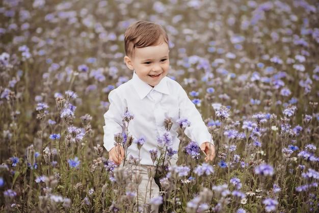 Gelukkige glimlachende jongen heeft een geweldige tijd op het gebied van bloemen