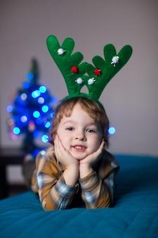 Gelukkige glimlachende jongen in een hertenkostuum dat kerstmis viert