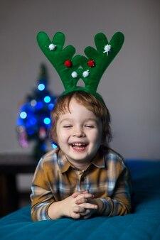 Gelukkige glimlachende jongen in een nieuwjaarskostuum van een hert dat kerstmis en nieuwjaar viert