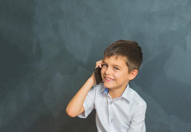 Gelukkige glimlachende jongen in een wit overhemd die op telefoon, kleine werkgever spreken.