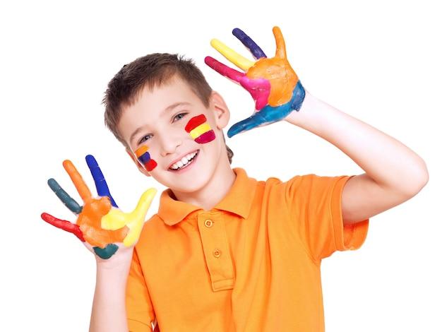 Gelukkige glimlachende jongen met geschilderde handen en gezicht in oranje t-shirt op wit.