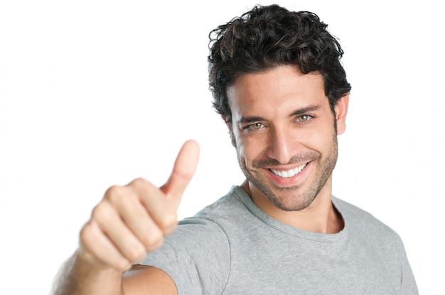Gelukkige glimlachende kerel die duim op handteken toont dat op witte achtergrond wordt geïsoleerd