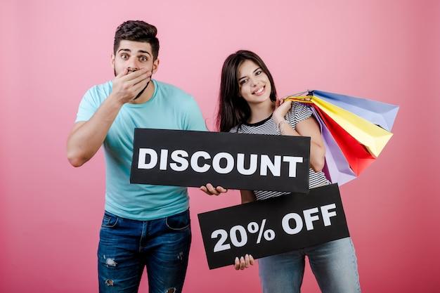 Gelukkige glimlachende knappe paarman en vrouw met korting 20% korting op teken en kleurrijke het winkelen zakken
