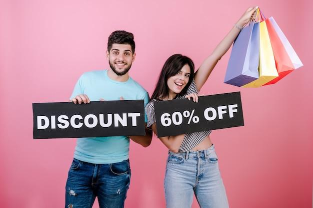 Gelukkige glimlachende knappe paarman en -vrouw met korting 60% korting op teken en kleurrijke het winkelen zakken