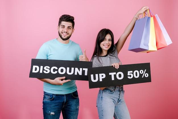 Gelukkige glimlachende knappe paarman en -vrouw met korting tot 50% ondertekenen en kleurrijke het winkelen zakken