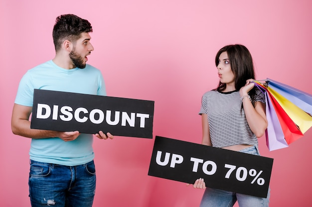 Gelukkige glimlachende knappe paarman en -vrouw met korting tot 70% ondertekenen en kleurrijke het winkelen zakken