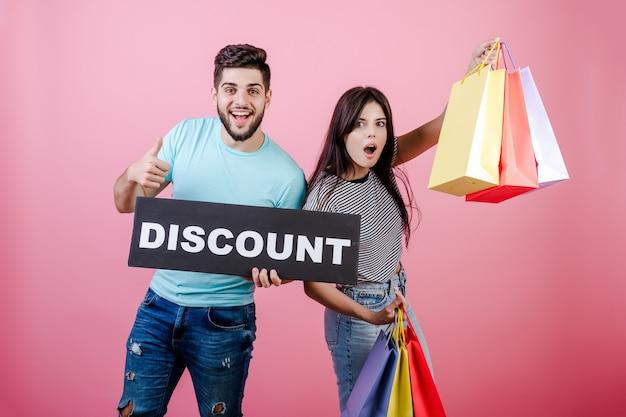 Gelukkige glimlachende knappe paarman en vrouw met kortingsbord en kleurrijke het winkelen zakken