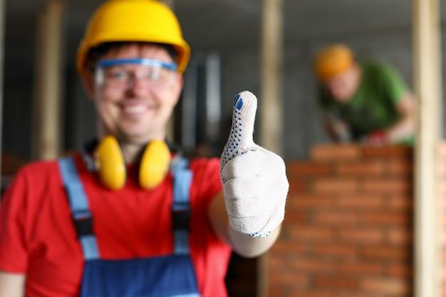Gelukkige glimlachende mannelijke arbeider die duim op gebaarclose-up tonen. fijne huisrenovatie of het beste service-concept voor aannemers
