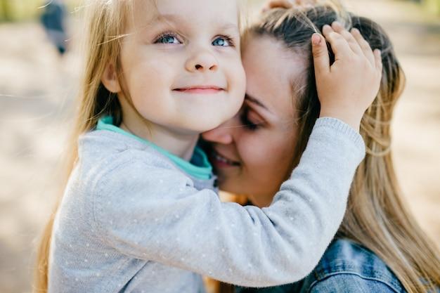 Gelukkige glimlachende moeder die haar mooie kleine dochter openlucht koestert. lifestyle familie.
