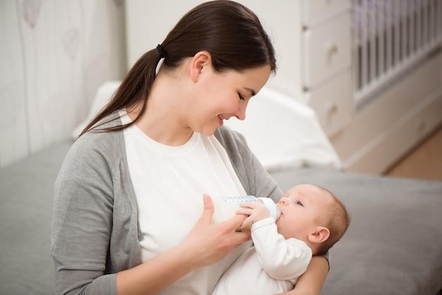 Gelukkige glimlachende moeder en baby die thuis op bed liggen en de baby eet melk.