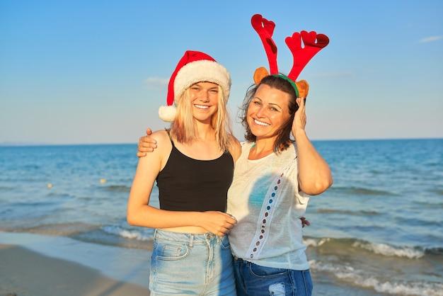 Gelukkige glimlachende moeder en tienerdochter in kerstmanhoed op het strand