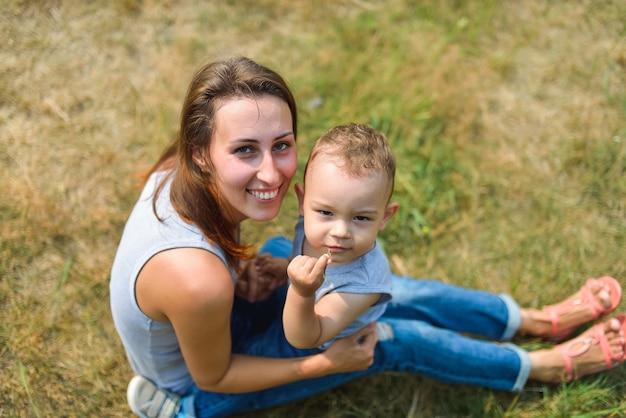 Gelukkige glimlachende moeder en zoonskindzitting op gras in de zomerdag