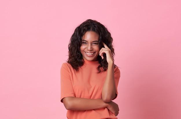 Gelukkige glimlachende mooie afrikaanse vrouw die camera bekijken die toevallige oranje t-shirt op roze dragen.