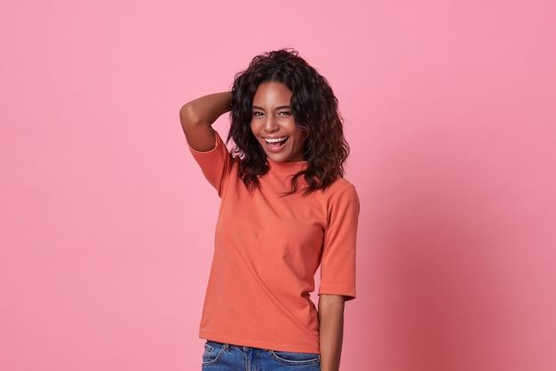 Gelukkige glimlachende mooie afrikaanse vrouw die camera bekijkt die toevallige oranje die t-shirt draagt op roze achtergrond wordt geïsoleerd.