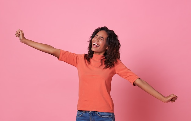 Gelukkige glimlachende mooie afrikaanse vrouw die toevallige oranje die t-shirt draagt op roze achtergrond wordt geïsoleerd.