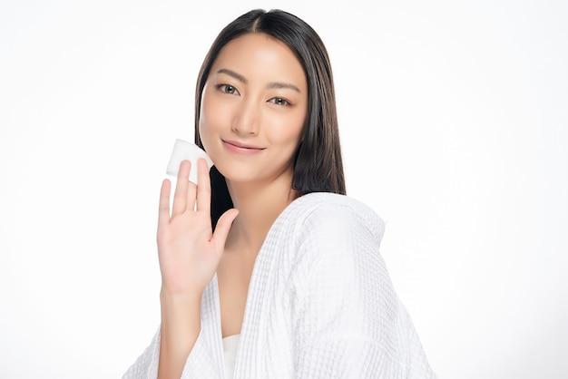Gelukkige glimlachende mooie aziatische vrouw die katoenen stootkussen schoonmakende huid gebruiken