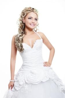 Gelukkige glimlachende mooie bruid in witte huwelijkskleding met kapsel en heldere make-up