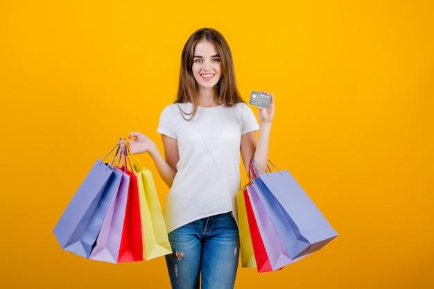 Gelukkige glimlachende mooie donkerbruine vrouw met kleurrijke document het winkelen zakken en creditcard die jeans en overhemd dragen die over geel worden geïsoleerd