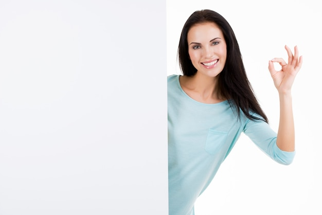 Gelukkige glimlachende mooie jonge vrouw die leeg uithangbord toont dat op wit wordt geïsoleerd
