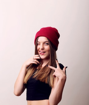 Gelukkige glimlachende mooie jonge vrouw die twee vingers of overwinningsgebaar toont, dat over beige muur wordt geïsoleerd