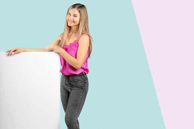 Gelukkige glimlachende mooie jonge vrouw in roze slimme toevallige kleding die leeg uithangbord of copyspace voor slogan of tekst tonen