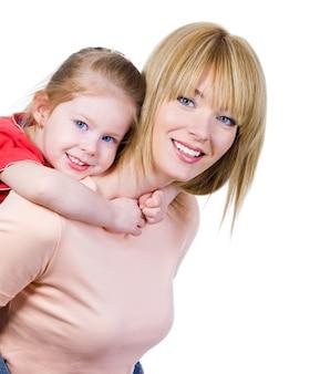 Gelukkige glimlachende mooie moeder met klein mooi geïsoleerd meisje op haar hals -