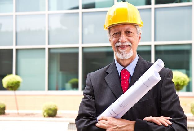 Gelukkige, glimlachende oudere architect die uit eruit ziet