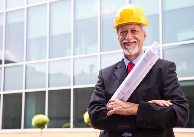 Gelukkige, glimlachende oudere architect die uit kijkt
