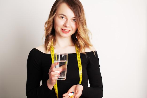 Gelukkige glimlachende positieve vrouw die de pil eet en het glas water in de hand, in haar huis houdt