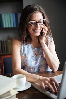 Gelukkige glimlachende rijpe vrouw in oogglazen die op de telefoon spreken