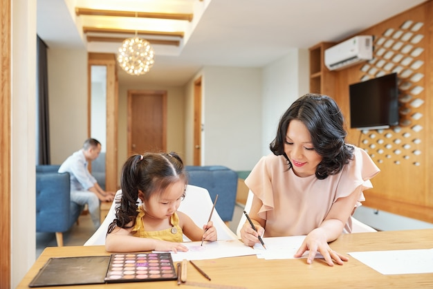 Gelukkige glimlachende vietnamese moeder en dochter die palet gebruiken wanneer thuis samen pijn, vader die op achtergrond werkt