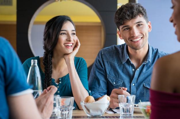 Gelukkige glimlachende vrienden die lunch hebben