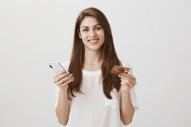 Gelukkige glimlachende vrouw bestelt online via smartphone-app, met creditcard en mobiele telefoon