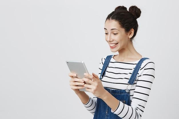 Gelukkige glimlachende vrouw die digitale tabletvertoning bekijkt